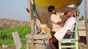 HAMPI, INDIA - APRIL 2013: Local barber at work stock footage