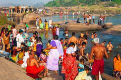 Indian people bathing and washing. HAMPI, INDIA - FEBRUARY 20, 2012: Indian people bathing and washing their clothes in the river in India stock image