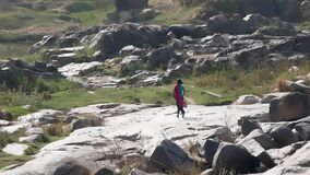 Hampi, India - January 26, 2019: A local girl runs in a hurry barefoot on stones.