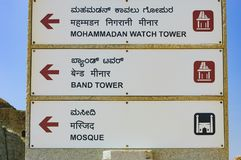Signpost to Towers in Hampi, India. Hampi, India - November 20, 2012: Signpost for tourists with the pointer to Mohammadan Watch Tower, Band Tower and Mosque in Royalty Free Stock Photography