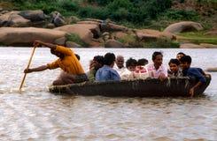 Hampi Indien: Folk som korsar floden i en fullsatt roddbåt för gammal stil arkivbilder