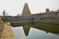 Virupaksha Temple - Tower Reflection on the temple pond. Hampi is known for its amazing landscapes embedded with boulders amid river and the mountains. The stock photo