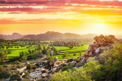 Hampi valley in India. View to Rice plantation from top of Hanuman monkey temple on hill at sunset in Hampi, Karnataka, India
