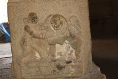 Hampi Vittala Temple pillar carving of human fighting with a lion. This is a stone pillar carving of human male fighting with a lion. This pillar is in Hampi Royalty Free Stock Photography