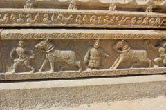 Hampi Vittala Temple Wall carving of humans taking decorated horses for trading Stock Photo