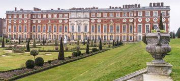 Hampton Court Palace from the gardens. Rear view of Hampton Court Palace from the gardens, showing decorative sculpted flower urn and topiary in the foreground Royalty Free Stock Image