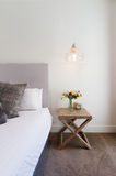 Hamptons styled bedside table with hanging pendant light in luxu Stock Image