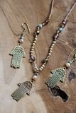 Hamsa Fatima hand metal pendant jewelry set. On wooden background royalty free stock image