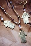 Hamsa Fatima hand metal pendant jewelry set. On wooden background royalty free stock images