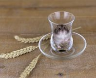 Hamster in a glass beaker on a wooden surface with wheat stalks Royalty Free Stock Photography