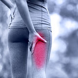 Hamstring sprain or cramps. Running sports injury with female runner. Closeup of woman back thigh stock photo