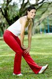 Hamstring Stretch. A young sporty woman stretching her legs in the park (shallow depth of field used royalty free stock photo