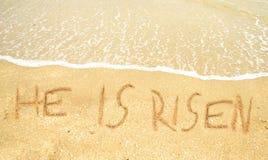 Han är uppstiget skriftligt i sanden för easter Royaltyfri Bild
