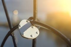 Han belägger med metall låset i form av en vit hjärta kedjas fast till gallret av bron i heder av förälskelse och lojalitet I royaltyfri fotografi
