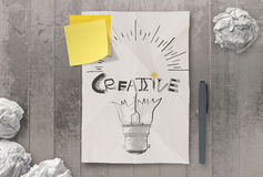 Han drawn light bulb and CREATIVE word design on clumpled paper Stock Image