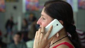 Han kvinnan i en röd klänning talar vid telefonen Kvinnan i det väntande rummet r stock video