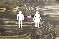 Han och hon klipps ut ur papper och i mitt en hjärta på en mörk träbakgrund illustration av förhållandet mellan a royaltyfria foton