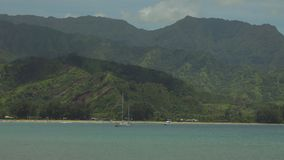 Hanalei Bay with Green Mountains in the Background, Kauai, Hawaii, USA. Hanalei Bay, on the Hawaiian island of Kauai, is shown in a daytime view, with boats in stock video footage