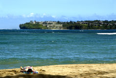 Hanalei Bay and Resort. Lone sun bather lays on the beach.  Hanalei Bay seperates her from the Hanalei Bay Resort on opposite shore line Royalty Free Stock Photo