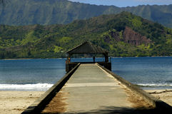 Hanalei Pier on Kauai, Hawaii. Hanalei Pier extends out into the blue ocean.  Mountains and blue sky fill background.  Concerete pier ends with topped pavillion Stock Photo