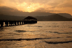 Hanalei Pier at sunset. Sun setting behind Na Pali mountains with a silhouette of Hanalei pier in the foreground and the sun reflecting on the ocean royalty free stock image