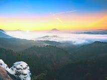 Hanar som täckas med nytt pulver, snöar, den dimmiga dalen stenig rock Royaltyfri Bild