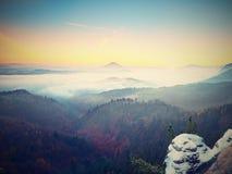 Hanar som täckas med nytt pulver, snöar, den dimmiga dalen stenig rock Arkivfoto