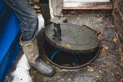 Hand öffnet Abwasserkanalluke im Yard Lizenzfreie Stockfotos