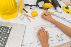 Hand över konstruktionsplan med det gula hjälm- och teckningshjälpmedlet arkivbilder