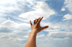 Hand 02. Open hand over blue sky and white clouds Royalty Free Stock Photo