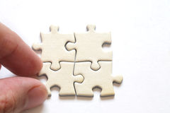 Hand with 4 puzzle close up Stock Photos