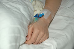 A hand. Womans hand on white hospitals bed royalty free stock images