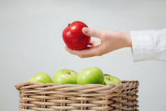 Hand above basket  with green apples and red. Basket with green apples and one red  in hand Stock Photo