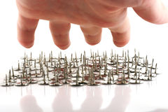 Hand above thumb tacks - drawing pins. Isolated on white royalty free stock photo