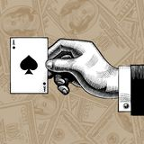 Hand with the ace of Spades playing card on the dollars bank not Royalty Free Stock Image