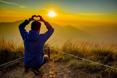 Hand acting heart shape with sunset background. Man acting heart hand shape in San Knok Wua hill at Khao Laem National Park Thailand with sunrise background royalty free stock photos