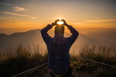 Hand acting heart shape with sunset background. Man acting heart hand shape in San Knok Wua hill at Khao Laem National Park Thailand with sunrise background stock photography