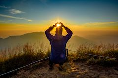 Hand acting heart shape with sunset background. Man acting heart hand shape in San Knok Wua hill at Khao Laem National Park Thailand with sunrise background stock photos