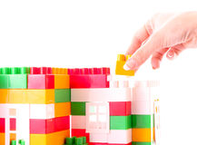 Hand add toy brick to toy building Royalty Free Stock Photos