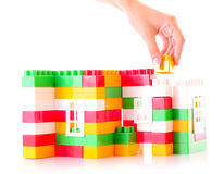 Hand add toy brick to toy building Stock Photography