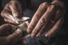Hand of addict man with money buying dose of cocaine or heroine or another narcotic from drug dealer. Drug abuse and traffic. Concept, toned stock photo