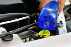 Hand adding auto glass cleaner for car Stock Photos