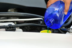 Hand adding auto glass cleaner for car Stock Image