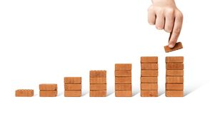 Hand adding brick stacking as step stair Royalty Free Stock Image