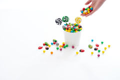 Hand adding candy to bucket. Female hand adding candy to a bucket full of candy with candy spilling over stock photos