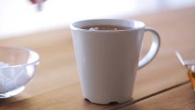 Hand adding sugar to cup of tea or coffee. Unhealthy eating and drinks concept - hand adding sugar to cup of tea or coffee stock footage