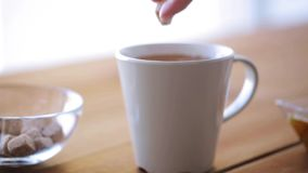 Hand adding sugar to cup of tea or coffee. Unhealthy eating and drinks concept - hand adding sugar to cup of tea or coffee stock video footage