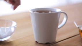 Hand adding sugar to cup of tea or coffee. Unhealthy eating and drinks concept - hand adding sugar to cup of tea or coffee stock video