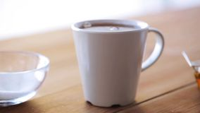Hand adding sugar to cup of tea or coffee. Unhealthy eating and drinks concept - hand with teaspoon adding sugar to cup of tea or coffee stock footage