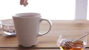 Hand adding sugar to cup of tea and honey on table. Unhealthy eating and drinks concept - hand adding sugar to cup of tea and honey on wooden table stock footage